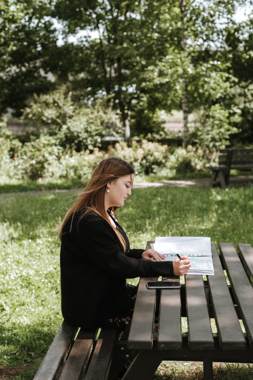Girl sitting at a picnic table.
